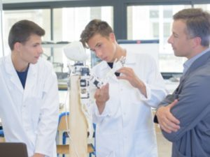 Scientific students showing an electronic device